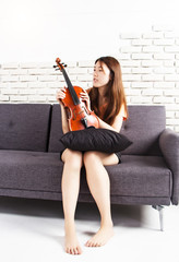 The young lady is sitting on sofa and hold checking violin,prepare for parctice,at studio music room.