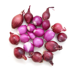 A group of small red pearl onions on a white background.