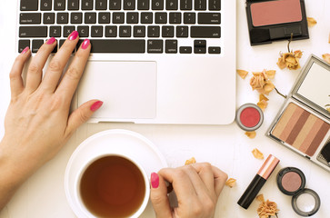 Woman holding coffee mug in hand and working on laptop. Fashion blogger concept, flat lay, top view