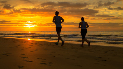 Couple are running on the beach at sunrise.
