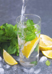 Glass of aced water with lemon and mint. Water drink pouring into glass