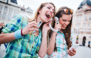 Listening to music. Two girls have fun with mobile phone. Lifestyle, fashion, technology