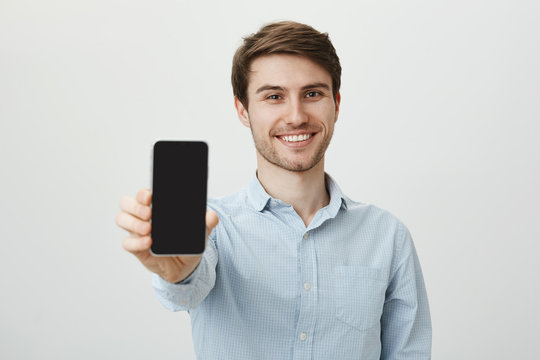 If you seek new phone, buy this model. Portrait of cheerful attractive white male with bristle, pulling hand towards camera and showing smartphone, smiling broadly over gray background