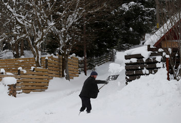 A man shovels snow in Carbeth, in Scotland
