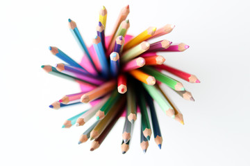Bunch of multicolored pencils in the plastic glass on white background, view from top