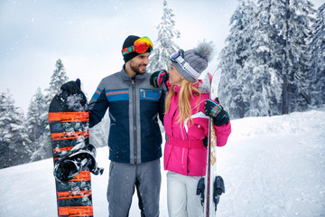 couple skiing and snowboarding enjoying in snowy mountains