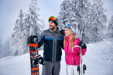 smiling couple together skiing on snowy mountain and looking something in distance