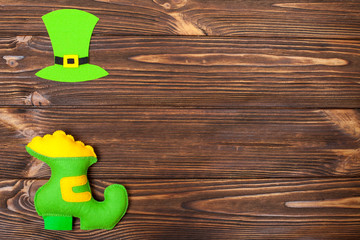 St. Patrick's Day theme colorful horizontal banner. Green leprechaun hat and shoe with gold on brown wooden background. Felt creft elements. Copy space. For greeting card,congratulation banner