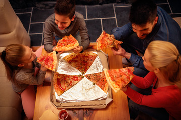 Top view of family eating pizza slices for the dinner