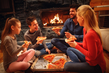 parents and children have fun and eating pizza together