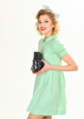 Woman with retro hair, makeup and old camera