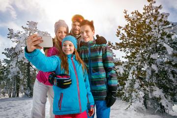 Winter, ski, snow and fun - family enjoying ski holiday. Mobile photo. Selfie