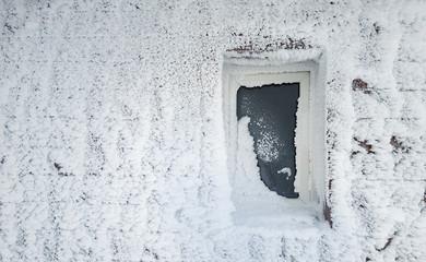 frozen window of house in winter scene