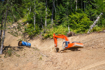 Photo of working excavator in summer day in forest