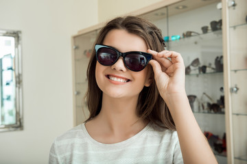 Girl seeks new sunglasses to accent her style. Indoor shot of cute feminine caucasian girl in store peaking new trendy eyewear, trying them on and enjoying how they match her face