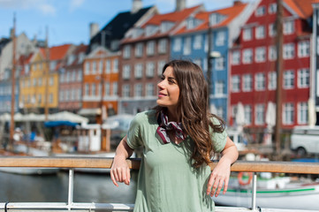 Young tourist woman, sitting at the Nyhavn harbor pier Copenhagen, Denmark. Visiting Scandinavia, famous European destination.