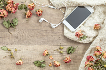 White knitting wool, dried roses flowers, mobile phone and headphones