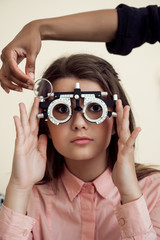 Horizontal shot of interested and curious caucasian girl on appointment with eye care specialist wearing phoropter while ophthalmologist checking her vision, sitting over yellow background
