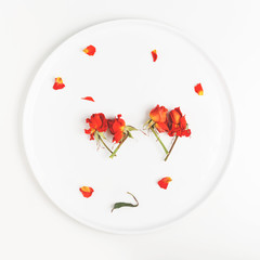 two images of a heart made of buds of dry flowers of roses on a white plate