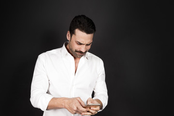 Young handsome man using a mobile phone with a negative attitude