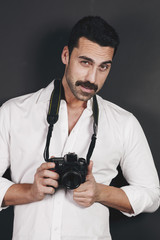 Young handsome photographer with beard and mustache studio portrait