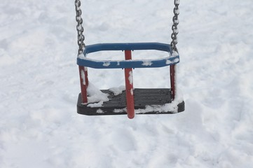 Detail of a swing chair in the snow (Pesaro, Italy)