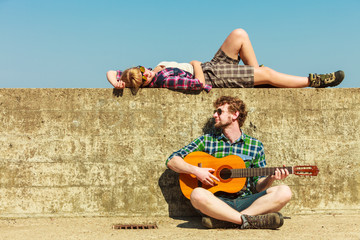 Young man playing guitar to his girlfriend by seaside