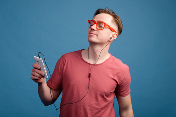 Young white man in red t-shirt and red glasses relaxing while listening to music in earphones from smartphone