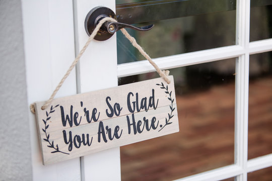 """""""We're So Glad You Are Here"""" Sign Hanging on Door Handle"""