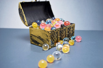 colorful balls spilling out of a treasure chest with bokeh