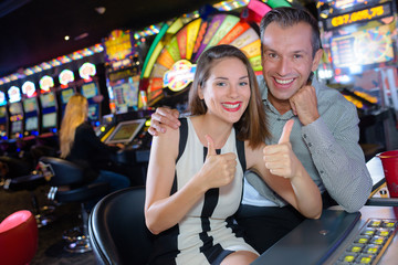 Couple giving thumbs up in casino