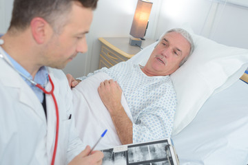 male doctor standing next to the patient and holding results