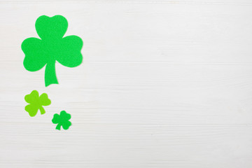 St. Patrick's Day theme colorful horizontal banner. Green shamrock leaves on white wooden background. Felt craft elements. Copy space. For greeting card, banner