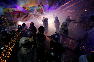 Participants wearing motorcycle helmets get sprayed with firecrackers, during the 'Beehive Firecrackers' festival at the Yanshui district, in Tainan