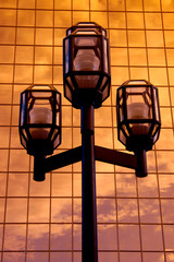 TRIPLE STREET LAMP AND GOLDEN SKY REFLECTION IN GLASS BUILDING