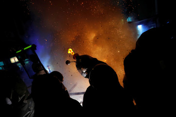 Participants wearing motorcycle helmets get sprayed with firecrackers, during the 'Beehive Firecrackers' festival at the Yanshui district in Tainan