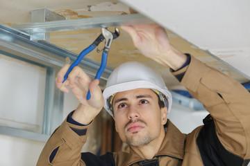 Workman using pliers on metal framework