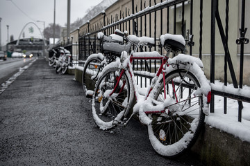 snow-covered bicycle locked to fence