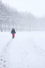 a young girl walking alone along a snow covered road leaving foot prints behind during a snow storm