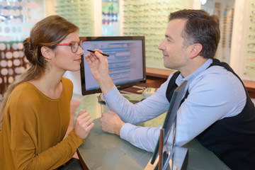 optometrist helping a pretty client to purchase eyeglasses