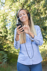 female runner smiles while listening to music in the forest