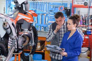 female motorbike mechanic inspecting the bike