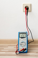 Voltage measuring with digital multimeter instrument on wall socket in home room.