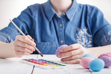 female artist painting traditional easter egg