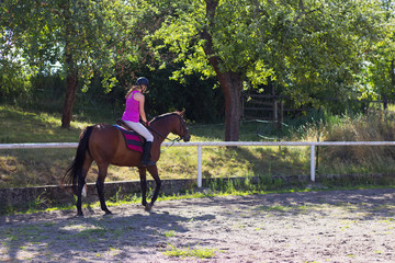 Woman is riding horse in paddock