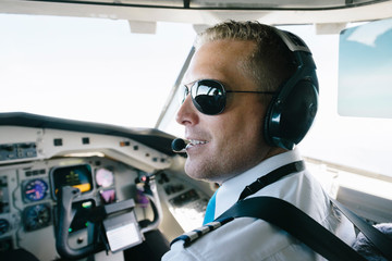 Confident smiling pilot wearing ear muff sitting in cockpit