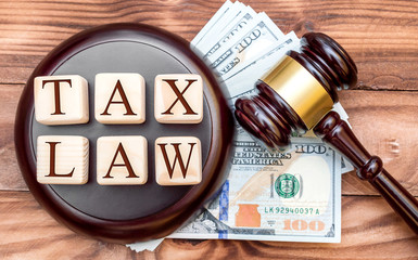 """Tax law concept. Words """"TAX LAW"""" with judge's gavel and money on the table. Top view."""