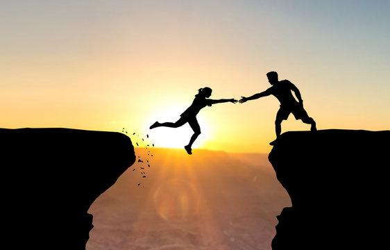 Mann reicht springender Frau die Hand vor Sonnenuntergang.