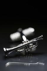 Foto op Canvas Muziek Trumpet cufflink on black