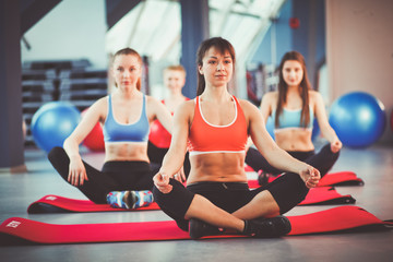 Sporty people sitting on exercise mats at a bright fitness studio. Sporty girls
